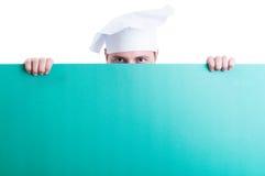 Cuisinier ou chef regardant au-dessus du mur vert avec l'espace publicitaire Images libres de droits
