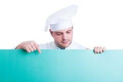Cuisinier ou chef tenant et montrant l'espace publicitaire vert Photos libres de droits