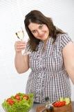 Cuisinier - plus le femme heureux de taille avec du vin blanc Photo stock