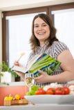 Cuisinier - plus le livre de cuisine heureux de fixation de femme de taille Images stock