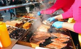 cuisinier tout en faisant cuire des saucisses dans la stalle de nourriture de rue photos libres de droits