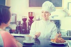 Cuisinier vendant la pâtisserie au client Photo stock