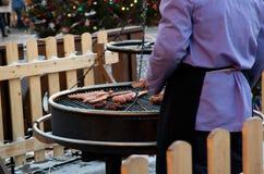 Cuisiniers d'homme sur les saucisses de gril photo libre de droits