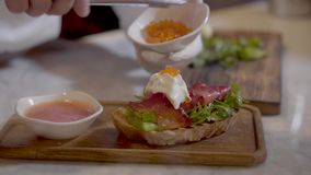 Cuisiniers de mains décorant le sandwich délicieux avec le caviar rouge Appétissant du pain délicieux avec les poissons, la crème banque de vidéos