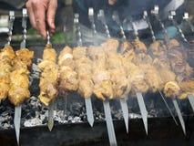 Cuisiniers de viande sur les charbons chauds dans la fumée Pique-nique en nature images stock