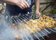 Cuisiniers de viande sur les charbons chauds dans la fumée Pique-nique en nature photos libres de droits