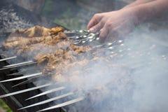Cuisiniers de viande sur les charbons chauds dans la fumée Pique-nique en nature photographie stock libre de droits