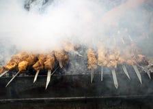 Cuisiniers de viande sur les charbons chauds dans la fumée Pique-nique en nature image stock
