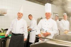 Cuisiniers et chef occupés d'équipe de cuisine professionnelle Images libres de droits