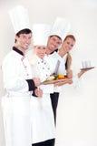 Cuisiniers et serveuse de sourire Photo stock