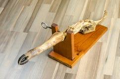 Cuisse de jambon de serrano finie au-dessus du bois Images stock