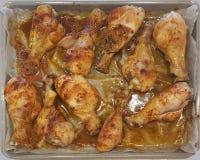 Cuisses de poulet cuites au four dans le four sur une palette à la sauce appropriée et arrosées avec des épices images libres de droits