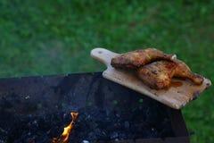 Cuisses grillées chaudes grillées de poulet sur un gril sur un conseil en bois avec de la fumée autour outdoors L'espace libre po photo stock