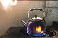 Cuisson à la vapeur de l'eau dans la bouilloire traditionnelle en métal sur le feu sur la cuisinière à gaz photo libre de droits