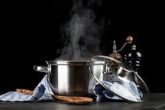Cuisson à la vapeur du pot sur le fond noir image stock