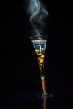 Cuisson à la vapeur du verre sur un fond noir Image libre de droits