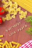 Cuisson avec amour Différents genres de pâtes sur le fond en bois Photographie stock libre de droits