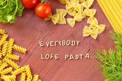 Cuisson avec amour Différents genres de pâtes sur le fond en bois Images libres de droits