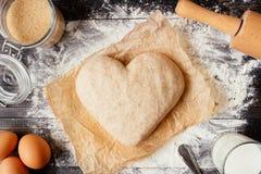 Cuisson avec amour Pâte dans la vue supérieure de forme de coeur Ingrédients de cuisson sur la table en bois Image libre de droits