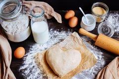 Cuisson avec amour Pâte dans la vue supérieure de forme de coeur Ingrédients de cuisson sur la table en bois Photo libre de droits