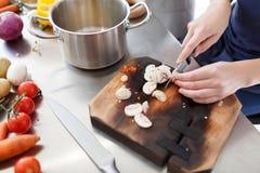 Cuisson avec des légumes Les mains femelles coupent des champignons sur un conseil en bois photo libre de droits