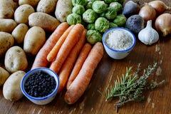 Cuisson avec des pommes de terre et des pousses de carottes Photos libres de droits