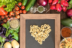 cuisson avec le concept d'amour Table de cuisine complètement des légumes, des épices et du vert avec le signe de coeur fait à pa Photographie stock