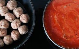 Cuisson crue de croquettes et de casseroles de sauce au jus photos libres de droits