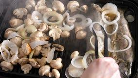 Cuisson d'un repas délicieux des poissons et des champignons grillés banque de vidéos