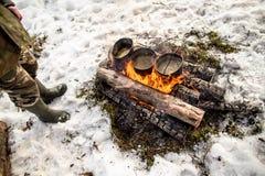 Cuisson dans une hausse d'hiver dans le chaudron accrochant au-dessus du feu Images stock