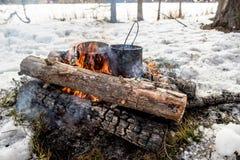 Cuisson dans une hausse d'hiver dans le chaudron accrochant au-dessus du feu Photo stock