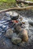 Cuisson dans une hausse dans le chaudron accrochant au-dessus du feu Image libre de droits
