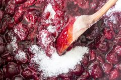 Cuisson de la confiture de cerise Remuez avec les cerises rouge foncé chaudes d'une cuillère en bois et le sucre blanc image libre de droits