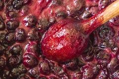 Cuisson de la confiture de cerise Remuez constamment avec les cerises rouge foncé de tourbillonnement d'une cuillère en bois et l photos stock