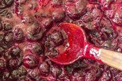 Cuisson de la confiture de cerise Remuez constamment avec les cerises rouge foncé de tourbillonnement d'une cuillère en bois et l images stock