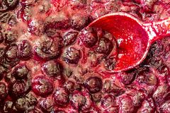 Cuisson de la confiture de cerise Remuez constamment avec les cerises rouge foncé de tourbillonnement d'une cuillère en bois et l image stock