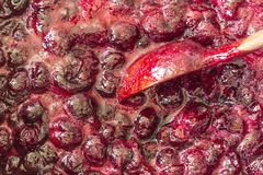 Cuisson de la confiture de cerise Remuez constamment avec les cerises rouge foncé de tourbillonnement d'une cuillère en bois et l photographie stock libre de droits