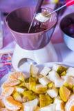 Cuisson de la fondue de chocolat avec des fruits Photo libre de droits
