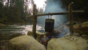 Cuisson de la nourriture dans le pot au-dessus du feu de camp clips vidéos