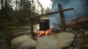 Cuisson de la nourriture dans le pot au-dessus du feu de camp banque de vidéos