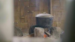 Cuisson de la nourriture dans le pot sur le feu sur le fond en bois de mur Préparation du dîner sur le feu dans la bouilloire dan clips vidéos
