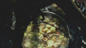 Cuisson de la nourriture sur un feu de camp dans la vie de forestCamp déplacement banque de vidéos