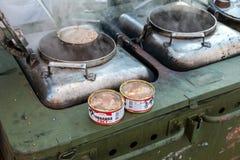 Cuisson de la nourriture sur une cuisine de champ militaire en conditions naturelles photos stock