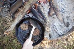 Cuisson de la saucisse au-dessus d'un feu de camp Images stock