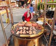Cuisson de la viande et des oeufs sur un gril énorme Photographie stock libre de droits