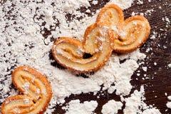 Cuisson des biscuits doux dans la forme du coeur sur la table en bois avec le flo Image stock