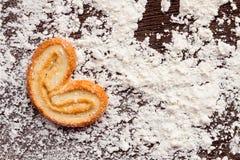 Cuisson des biscuits doux dans la forme du coeur sur la table en bois avec le flo Photographie stock libre de droits