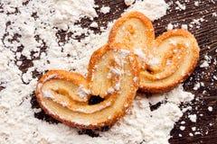 Cuisson des biscuits doux dans la forme du coeur sur la table en bois avec le flo Photo libre de droits
