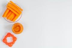 Cuisson des carottes écrasées pour le bébé sur la vue supérieure de fond blanc Images stock