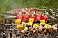 Cuisson des chiches-kebabs et des tomates sur des brochettes Photo libre de droits